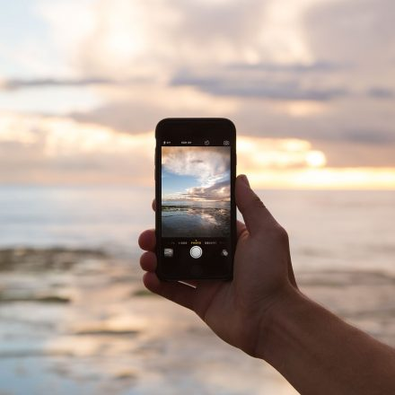 Touchscreen phone taking picture of the ocean at sunset Empowering Students to Stop Cell Phone Addiction Teaching Strategies for Today's Students (iGen or GenZ)